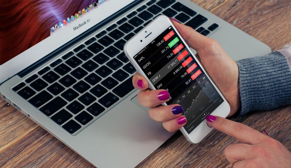 mão de mulher com celular e notebook - porque investir em mobile