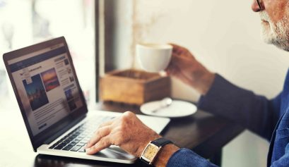 homem de negócios trabalhando no computador e tomando café - como impulsionar posts no Facebook
