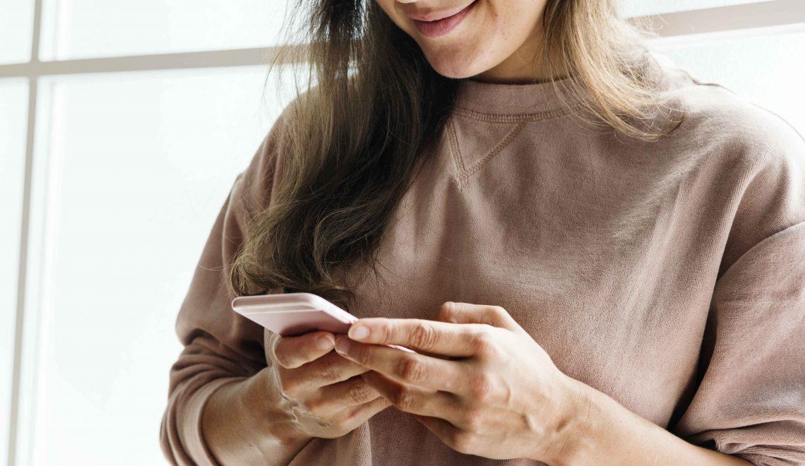 mulher mexendo no celular - como impulsionar posts no instagram