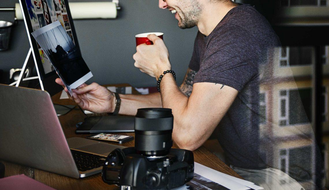 homem sorrindo com café na mão na mesa de trabalho - mudanças no jornalismo digital